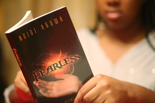 Ndidi Aguwa holds a copy of her book 'Fearless' at her home in Hopewell Junction on October 4, 2018. Fearless is her first book, but at 17 years old, the Our Lady of Lourdes Senior hopes to continuing to write and publish as she gets older.