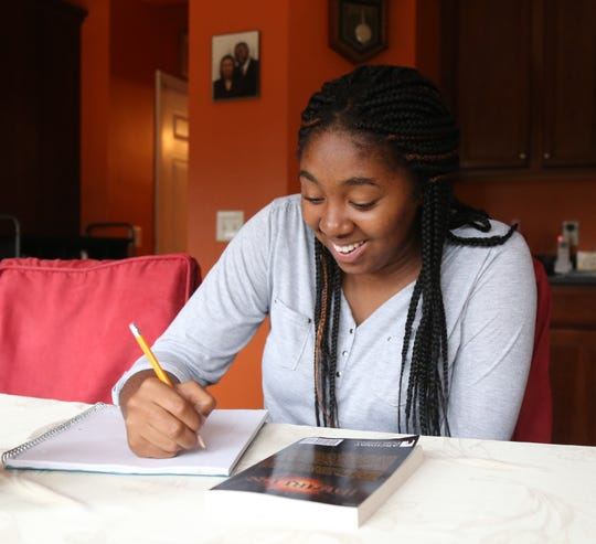 Ndidi Aguwa writes in her notebook at her home in Hopewell Junction on October 4, 2018. Ndidi recently published her first novel, 'Fearless'.