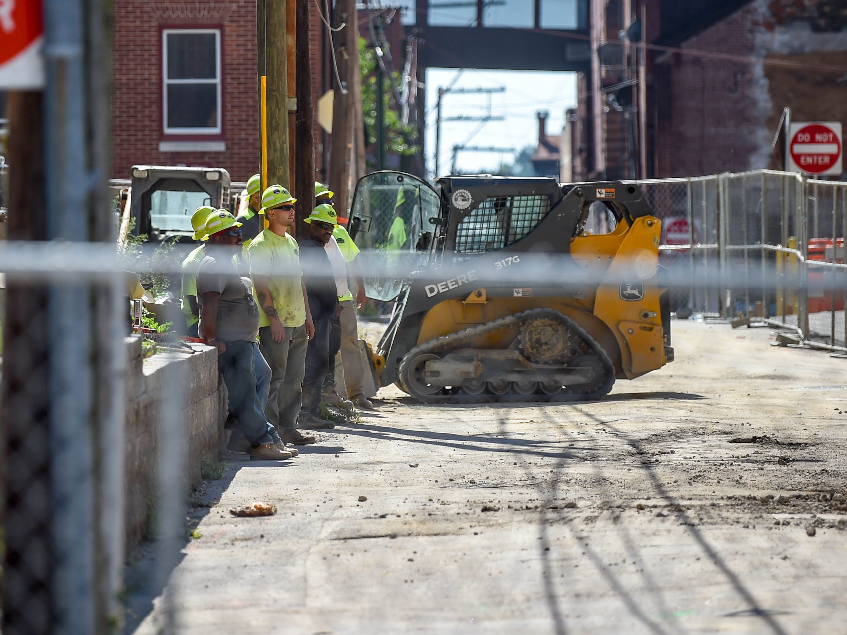Construction workers watch as the trackhoe lifts debris out of the way at the Yorktowne Hotel on October 4, 2018.