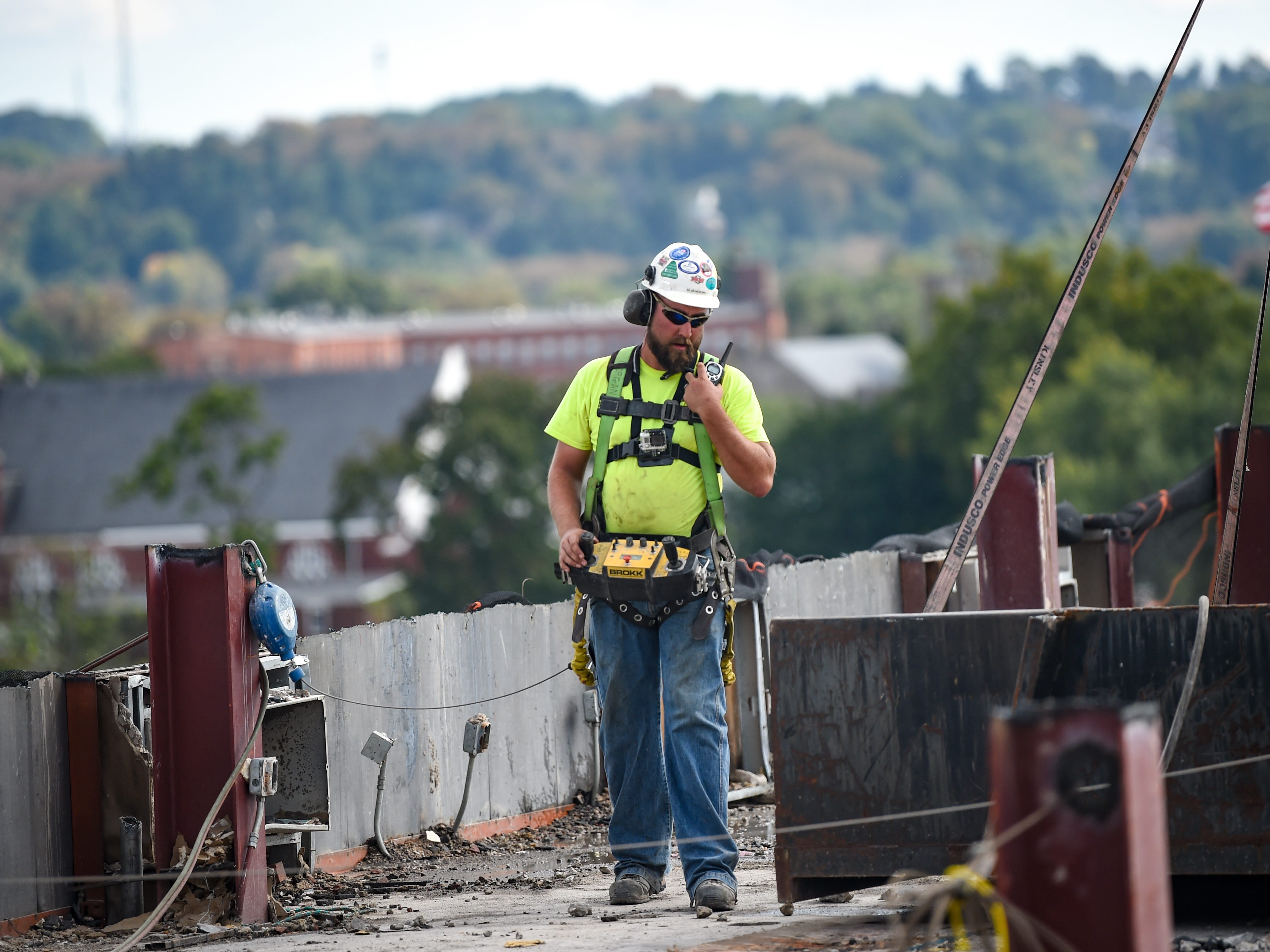 Silas Morgan, the Brokk specialist, communicates with the crane operator to move the robot at the Yorktowne Hotel on October 4, 2018.