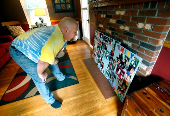 Jim MacDuff looks at a collage of photos of his stepdaughter Emily Short, who died in September at age 22 from a heroin overdose. He lives with Emily's mother, Tamara Irondequoit.