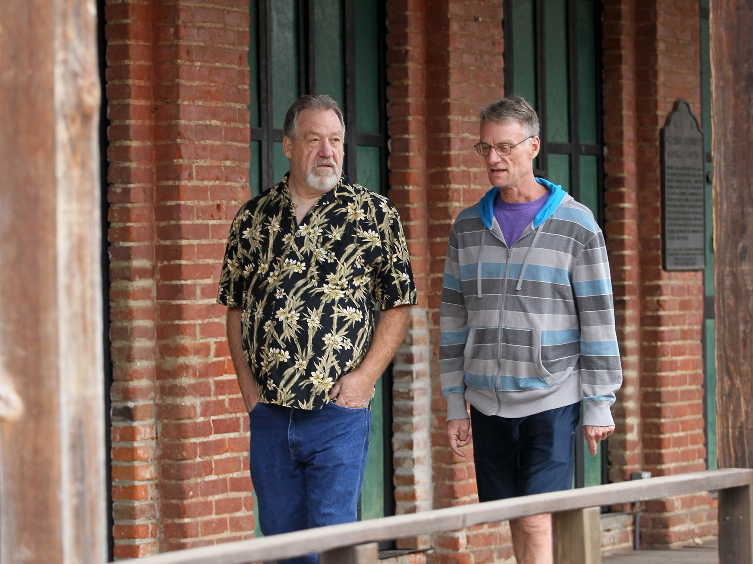 Tom Hinton, left, and Brad Hart, walk under the porch of the Shasta museum as they reflect on the time they organized one of the first drag queen shows in the Redding area in 1989. (Hung T. Vu/Special to the Record Searchlight)
