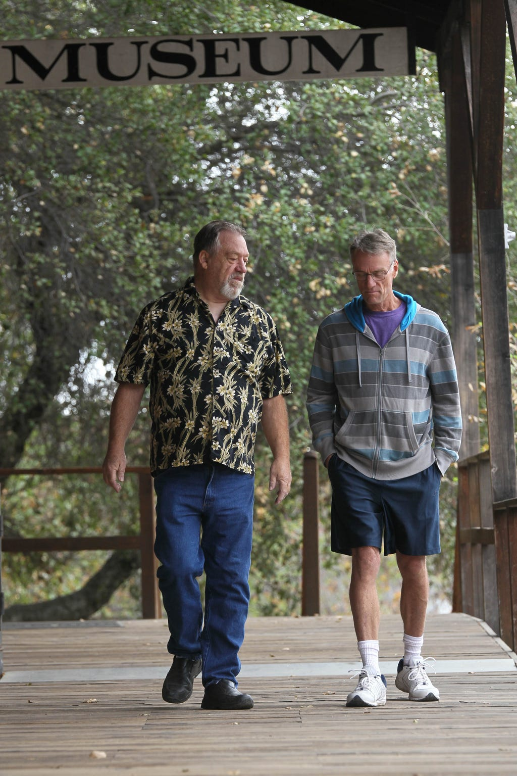 Tom Hinton, left, and Brad Hart, walk under the porch of the Shasta State Park museum as they reflect the time when they organized one of the first drag queen shows in the Redding area in 1989.