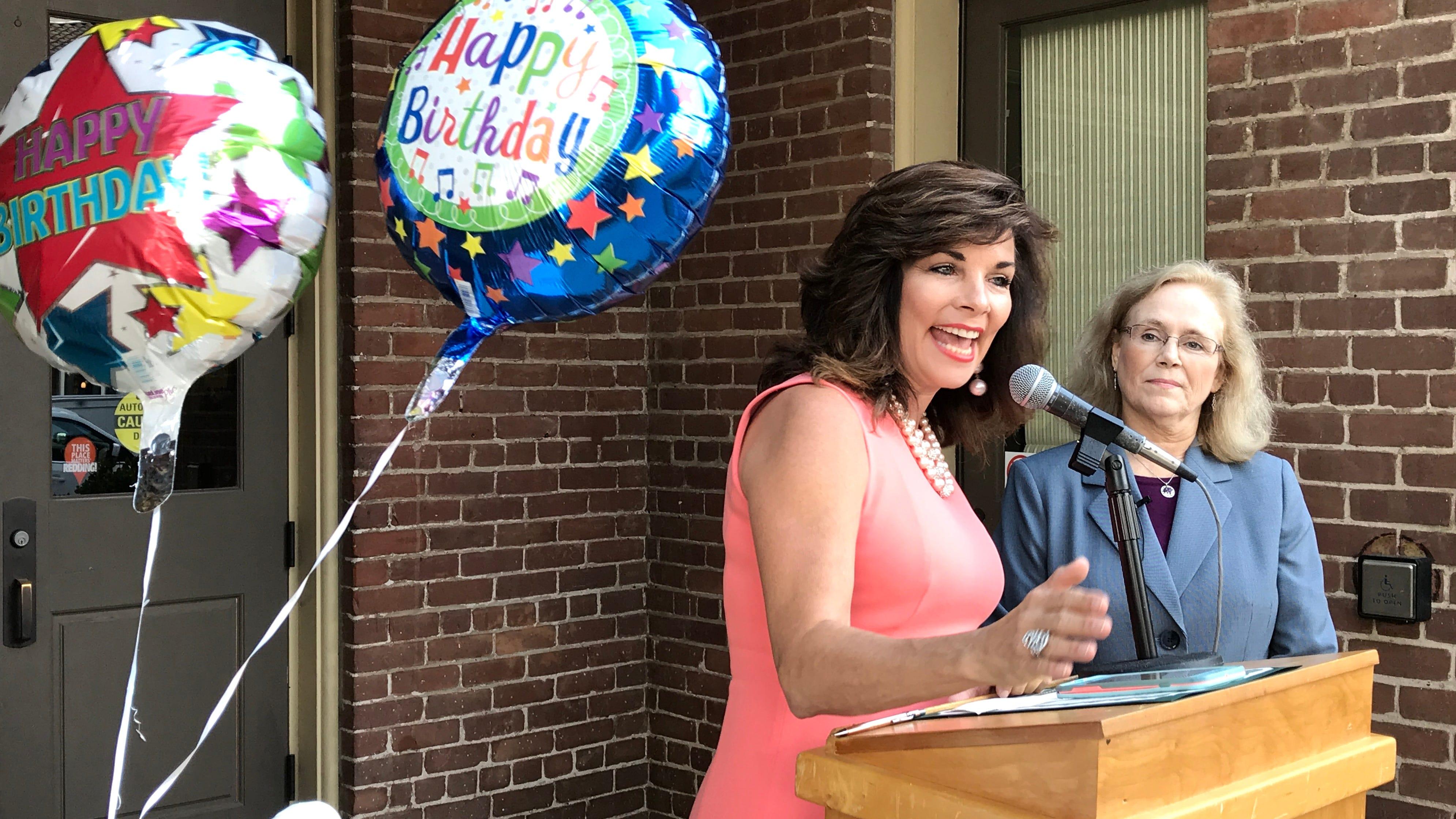 June Bell-Skeet, CEO of ILoveRedding.com, celebrates Redding's 131st birthday Thursday in front of Old City Hall beside Mayor Kristen Schreder.