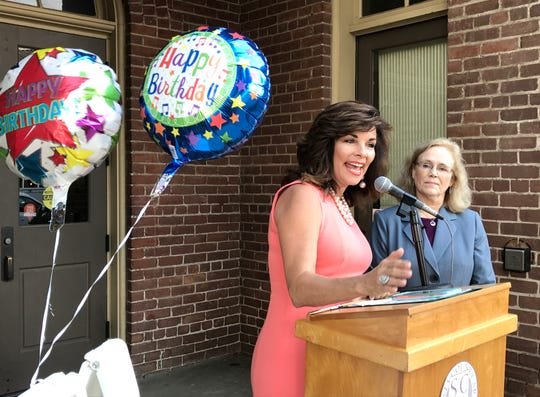 June Bell-Skeet, CEO of ILoveRedding.com, celebrates Redding's 131st birthday Thursday in front of Old City Hall beside Mayor Kristen Schreder.