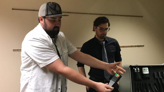 Dylan Lane, lead investigator with Concho Valley Paranormal, explains how the electromagnetic field reader works. Tyler Tennell, fellow investigator, waits to explain the next piece.