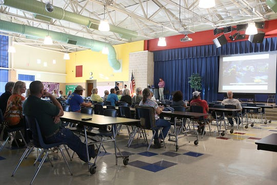 Residents watch a news clip about recycling during a public town hall meeting Thursday, Oct. 4, 2018, about the City's recycling program at Lincoln Middle School.