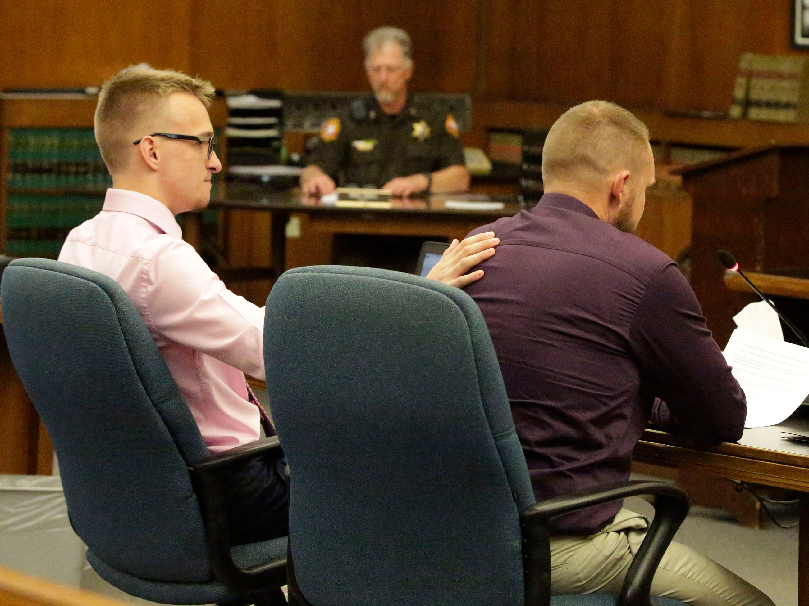 Joshua Mikula, left, puts his hand on his dad Charles Mikula, as the elder Mikula reads an impact statement in Sheboygan County Circuit Court Branch 1 during the sentencing hearing for Christy Rose Tuchel, Friday, October 5, 2018, in Sheboygan, Wis.