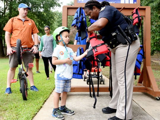 Brett Ediger learns how to put on a life jacket by Cpl. April Kelly during the Sheriff's Safety Town 10th Anniversary Super Safety Saturday in Shreveport.
