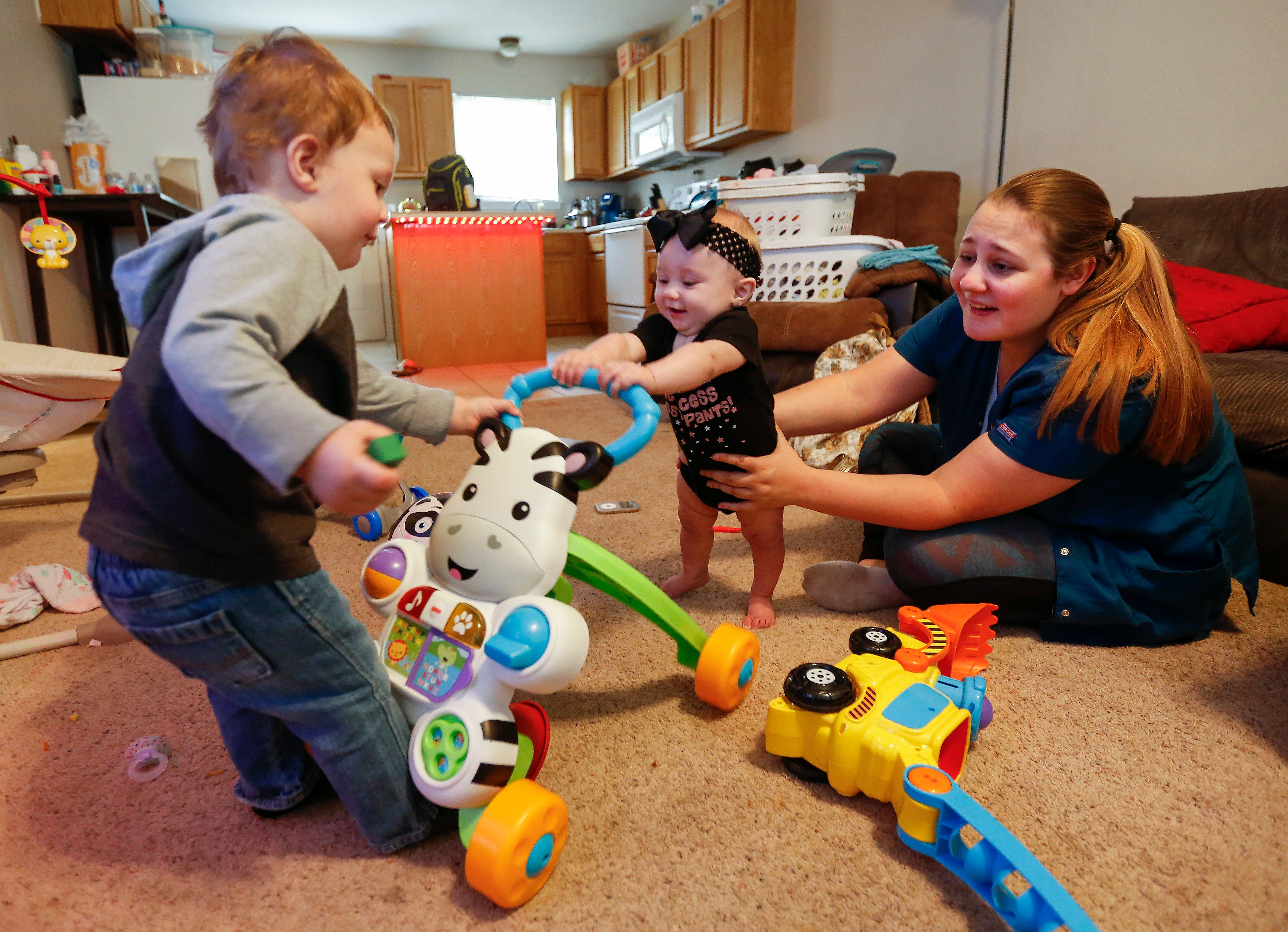 Annie Dillard steadies her daughter Moxxi Bateman, 7 months, as her son Axton Bateman, 18 months, pulls on a toy she was using to hold herself up at their home in Ozark on Wednesday, Sep. 27, 2018.