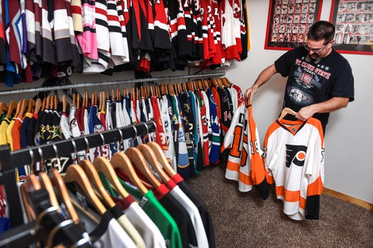 Heath Warnert, Sartell, shows some of the  hockey jerseys Wednesday, Oct. 3, in his massive collection.