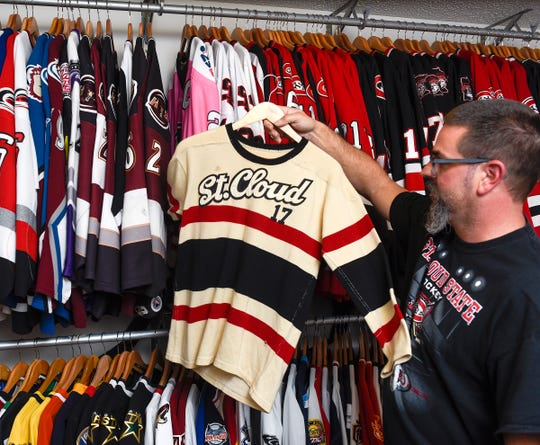 Heath Warnert, Sartell, shows an old St. Cloud State University hockey jerseys Wednesday, Oct. 3, that he acquired for his collection.