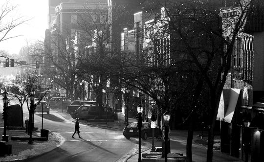 A pedestrian crosses St. Germain Street as the sun sets over downtown St. Cloud.