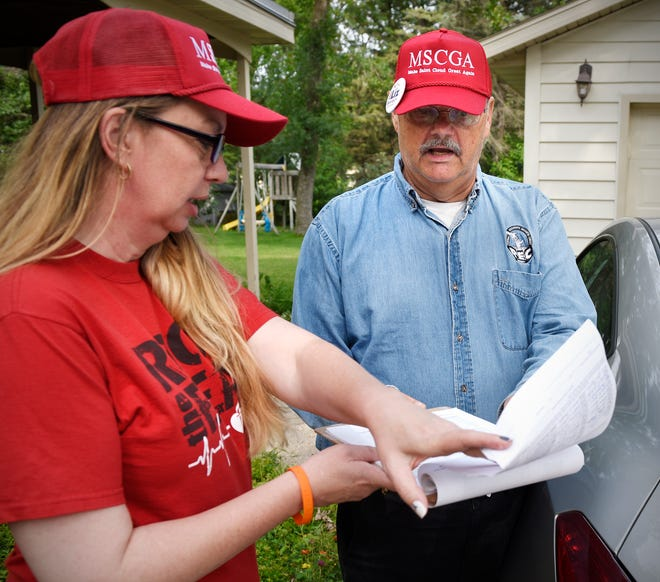 """Ward 2 candidate Liz Baklaich and Ward 1 candidate John Palmer look at a petition Friday, Aug. 3, to try to add a refugee resettlement resolution to the ballot. Baklaich made red hats that say """"Make St. Cloud Great Again"""" — a riff on President Donald Trump's """"Make America Great Again"""" hats."""