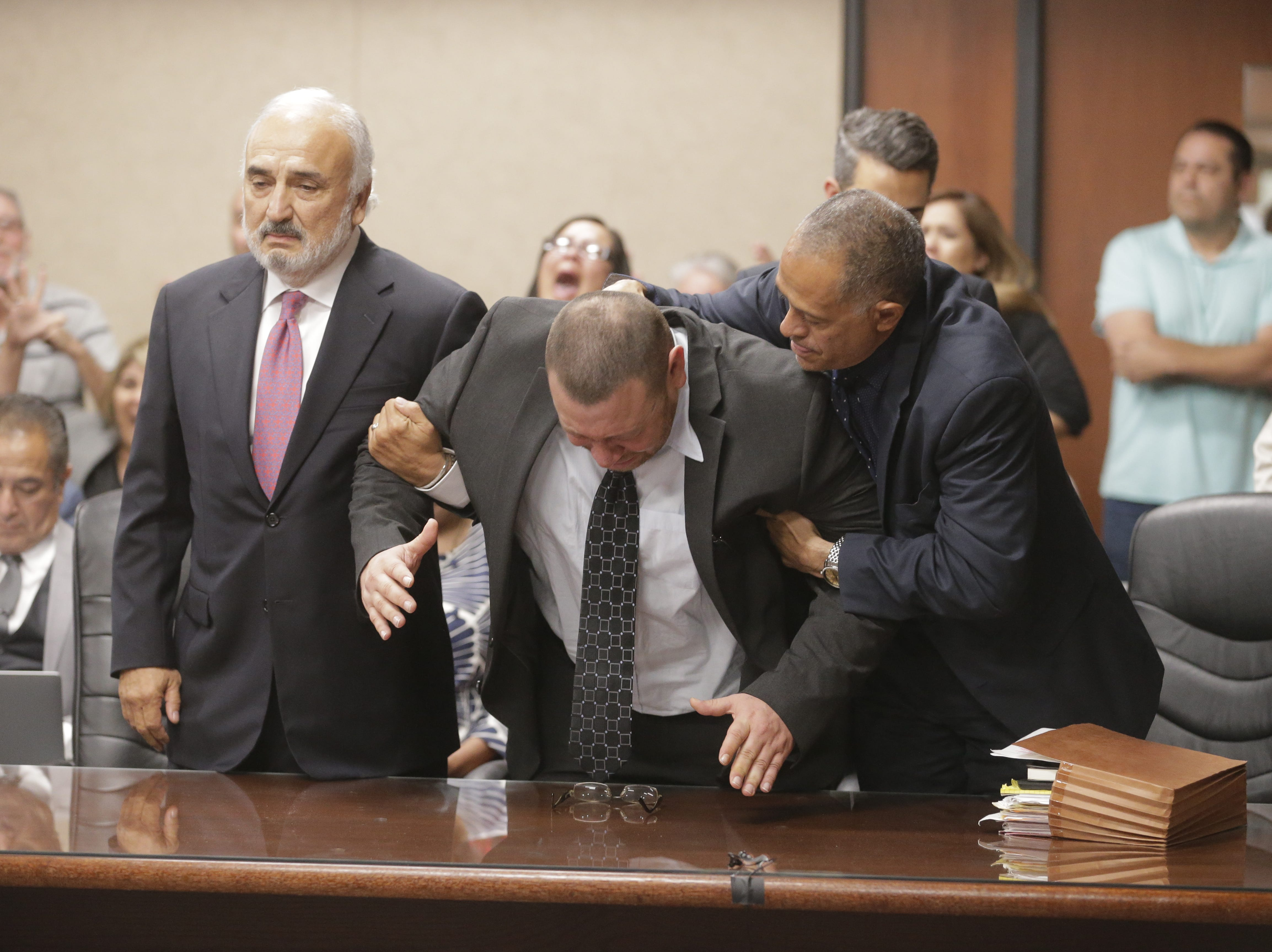 Defense attorneys Joe Spencer, left, and Felix Valenzuela help Daniel Villegas back to his feet after he collapsed when the verdict was read in his trial.