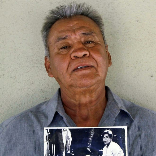 This photo provided by STORYCORPS shows Juan Romero holding a Los Angeles Times photograph that shows Romero with Sen. Robert F. Kennedy at the Ambassador hotel in Los Angeles moments after Kennedy was shot.