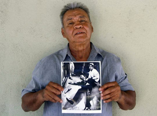 This photo provided by STORYCORPS shows Juan Romero holding a Los Angeles Times photograph that shows Romero with Sen. Robert F. Kennedy at the Ambassador hotel in Los Angeles moments after Kennedy was shot.   The Los Angeles Times reported Thursday, Oct. 4, 2018, that Romero died Monday in Modesto, California, at age 68.  Romero was a busboy in June 1968 when Kennedy walked through the Ambassador Hotel kitchen after his victory in the California presidential primary and an assassin shot him in the head. He held the mortally wounded Kennedy as he lay on the ground, struggling to keep the senator's bleeding head from hitting the floor.      (Jud Esty-Kendall/STORYCORPS via AP)