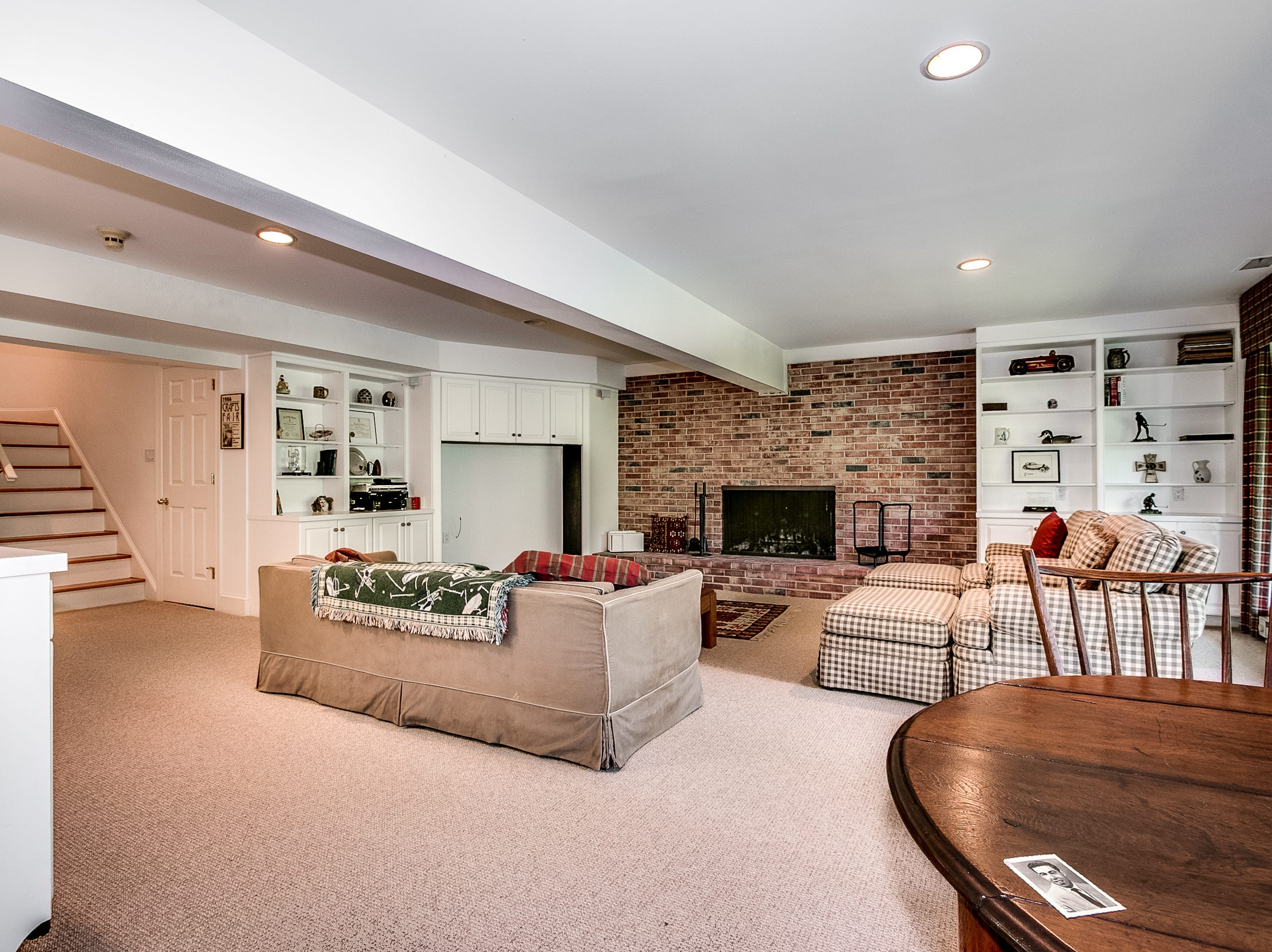 The lower level family room at 7 Brandywine Falls Road in Wilmington has a brick fireplace, built-in cabinetry and a kitchenette.