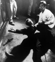 In this June 5, 1968 file photo,  Hotel busboy Juan Romero, right, comes to the aid of Senator Robert F. Kennedy,  as he lies on the floor of the Ambassador hotel in Los Angeles moments after he was shot.  The Los Angeles Times reported Thursday, Oct. 4, 2018, that Romero died Monday in Modesto, California, at age 68.  Romero was a teenage busboy in June 1968 when Kennedy walked through the Ambassador Hotel kitchen after his victory in the California presidential primary and an assassin shot him in the head. He held the mortally wounded Kennedy as he lay on the ground, struggling to keep the senator's bleeding head from hitting the floor. (Boris Yaro/Los Angeles Times via AP)