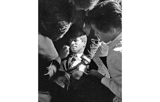FILE - In this June 5, 1968 file photo, Hotel busboy Juan Romero, right, comes to the aid of Senator Robert F. Kennedy,  as he lies on the floor of the Ambassador hotel in Los Angeles moments after he was shot.  The Los Angeles Times reported Thursday, Oct. 4, 2018, that Romero died Monday in Modesto, California, at age 68.  Romero was a teenage busboy in June 1968 when Kennedy walked through the Ambassador Hotel kitchen after his victory in the California presidential primary and an assassin shot him in the head. He held the mortally wounded Kennedy as he lay on the ground, struggling to keep the senator's bleeding head from hitting the floor. (Richard Drew/Pasadena Star News via AP)