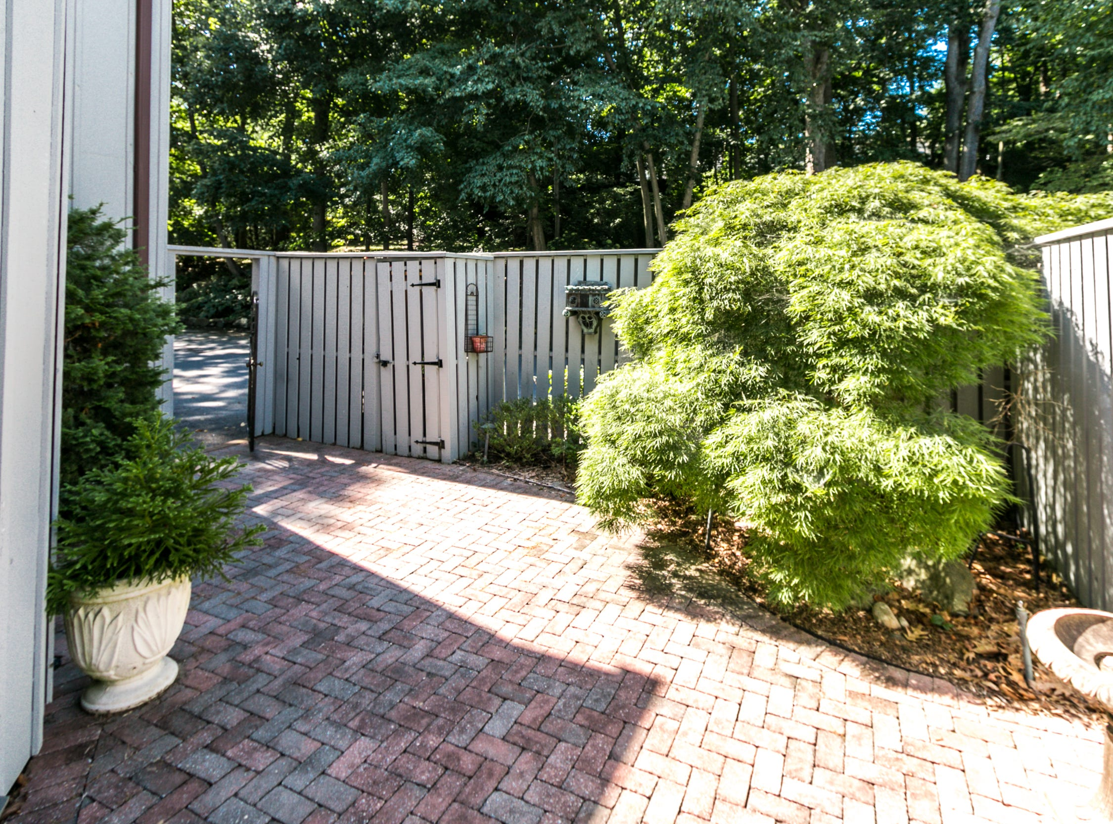 A private brick courtyard enclosed in a fence is the private entrance to this condo at 7 Brandywine Falls Road in Wilmington.