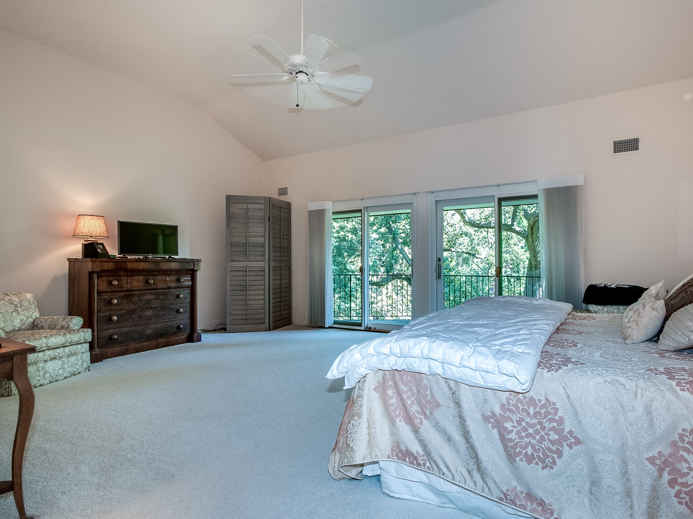 A large master bedroom has a balcony overlooking the Brandywine River at 7 Brandywine Falls in Wilmington.
