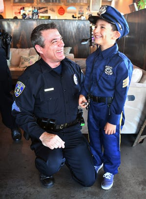 Wichita Falls Police Sergeant Harold McClure has his picture taken with Enrique Hernandez, 7, Friday morning at Frank & Joe's Coffee House during the Coffee with a Cop event.