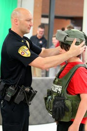Burkburnett police officer Zac Leonard adjust the SWAT helmet on Christopher Arbogast as he tries on the gear during Thursday nights Burkburnett ISD STEM Fair  held at Burkburnett High School.  The Science, Technology, Engineering, and Math fair was free to the public to attend