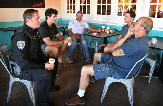Wichita Falls Police officer Clint Halloway visits with David Trimble, Chad Houck, center, Beau Byars and retired WFPD Sgt. Mike Yonts, right, during a Coffee With a Cop event Friday at Frank & Joe's Coffee House.