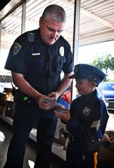 Wichita Falls Police officer Tim Johnson shares WFPD trading cards with Enrique Hernandez, 7, who wore a junior police uniform to a Coffee With a Cop event at Frank & Joe's Coffee House Friday morning.