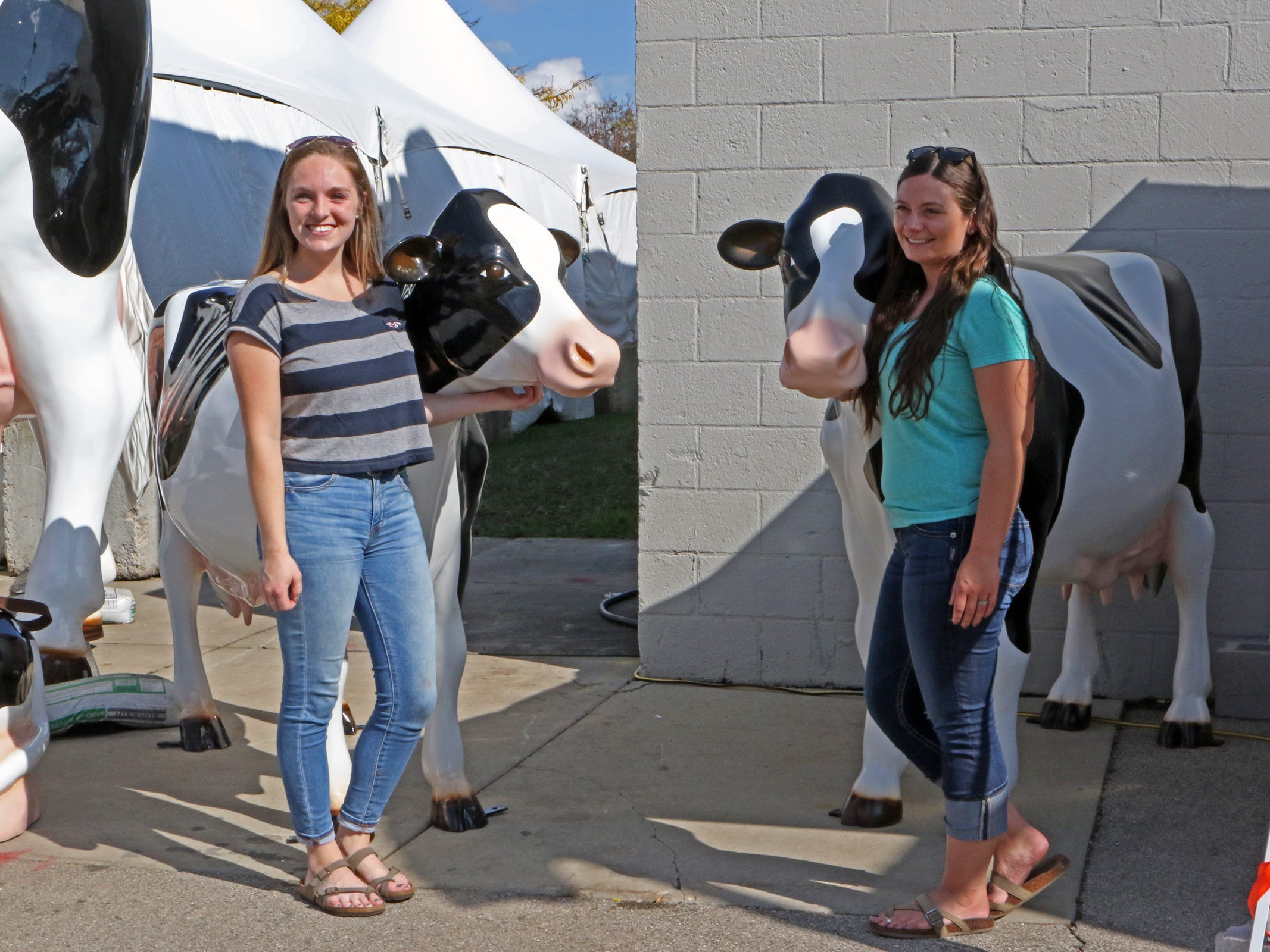 Karissa Vance (left) AND Marissa Olson, both from Oconomowoc, express their love of cows through a photo during World Dairy Expo on Oct. 3 in Madison.