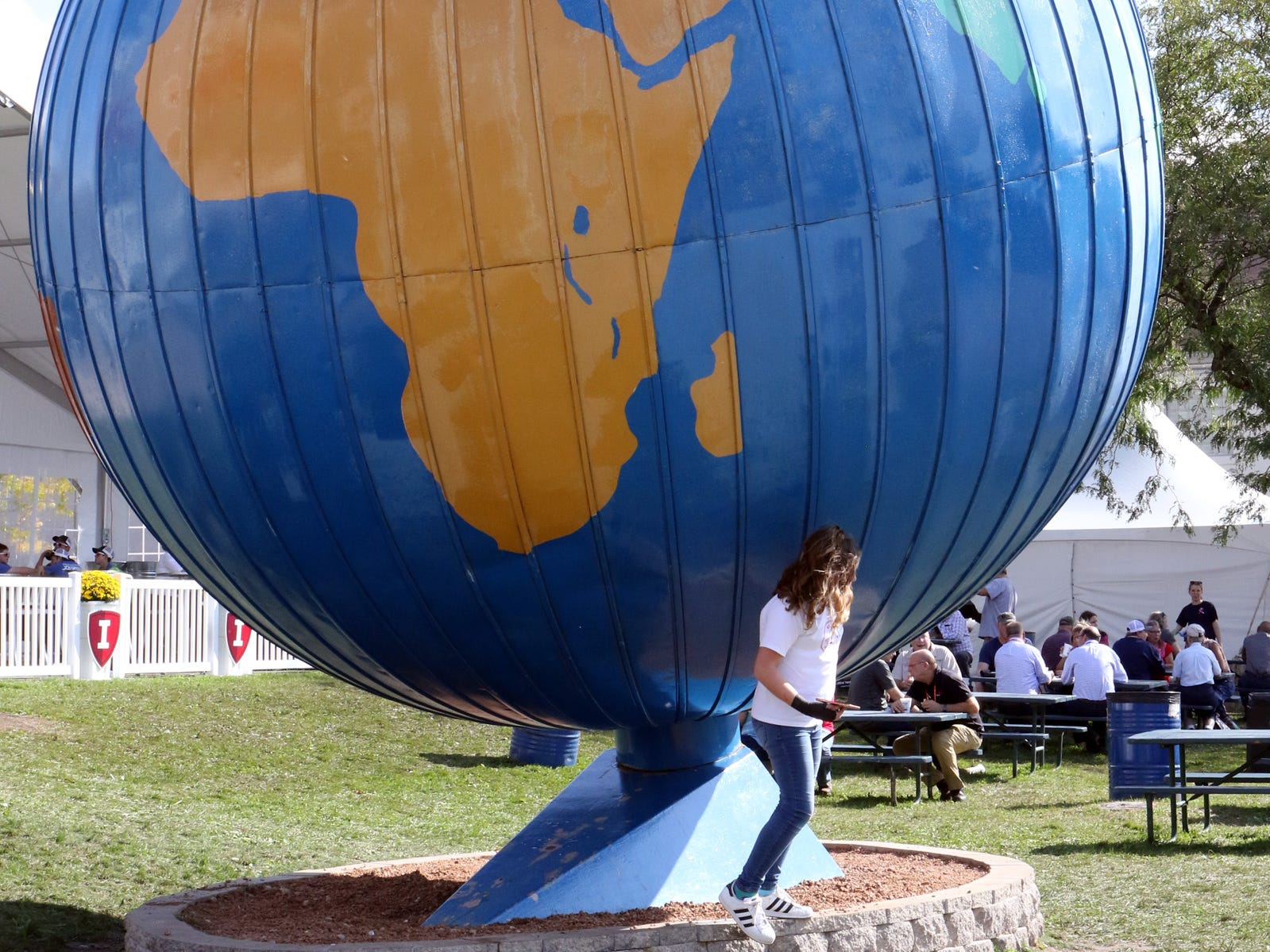 A young girl grabs a selfie under the giant globe at World Dairy Expo on Oct. 3, 2018, in Madison.