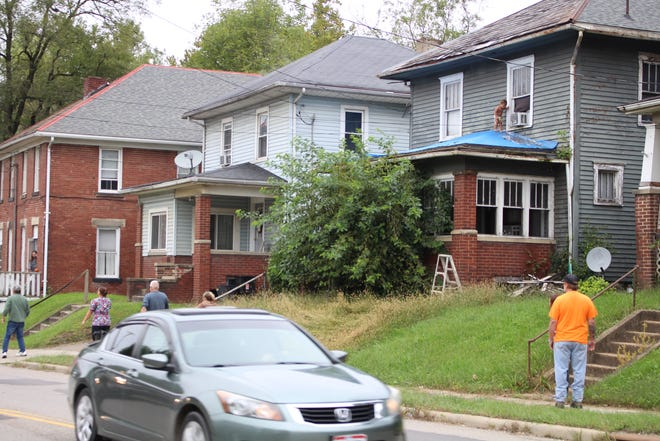 Passerbys and neighbors respond as a toddler wanders on the roof of a nearby house.