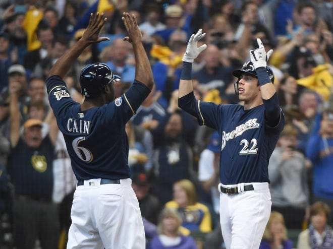 Christian Yelich celebrates with Lorenzo Cain after hitting a two-run home run against the Rockies in the third inning in Game 1 of the NLDS at Miller Park.