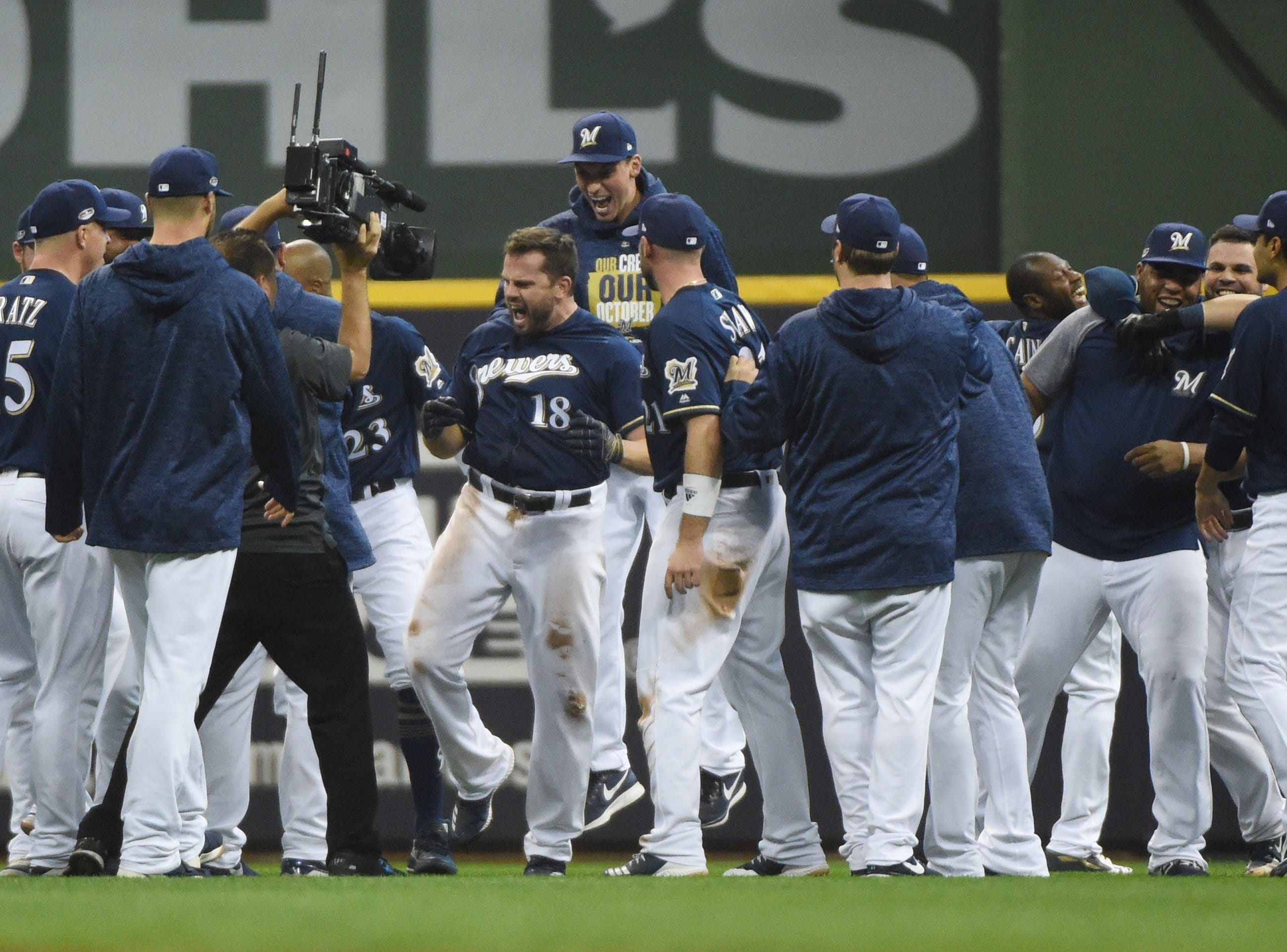 NLDS Game 1: Brewers players celebrate Mike Moustakas' walk-off single in the 10th inning.