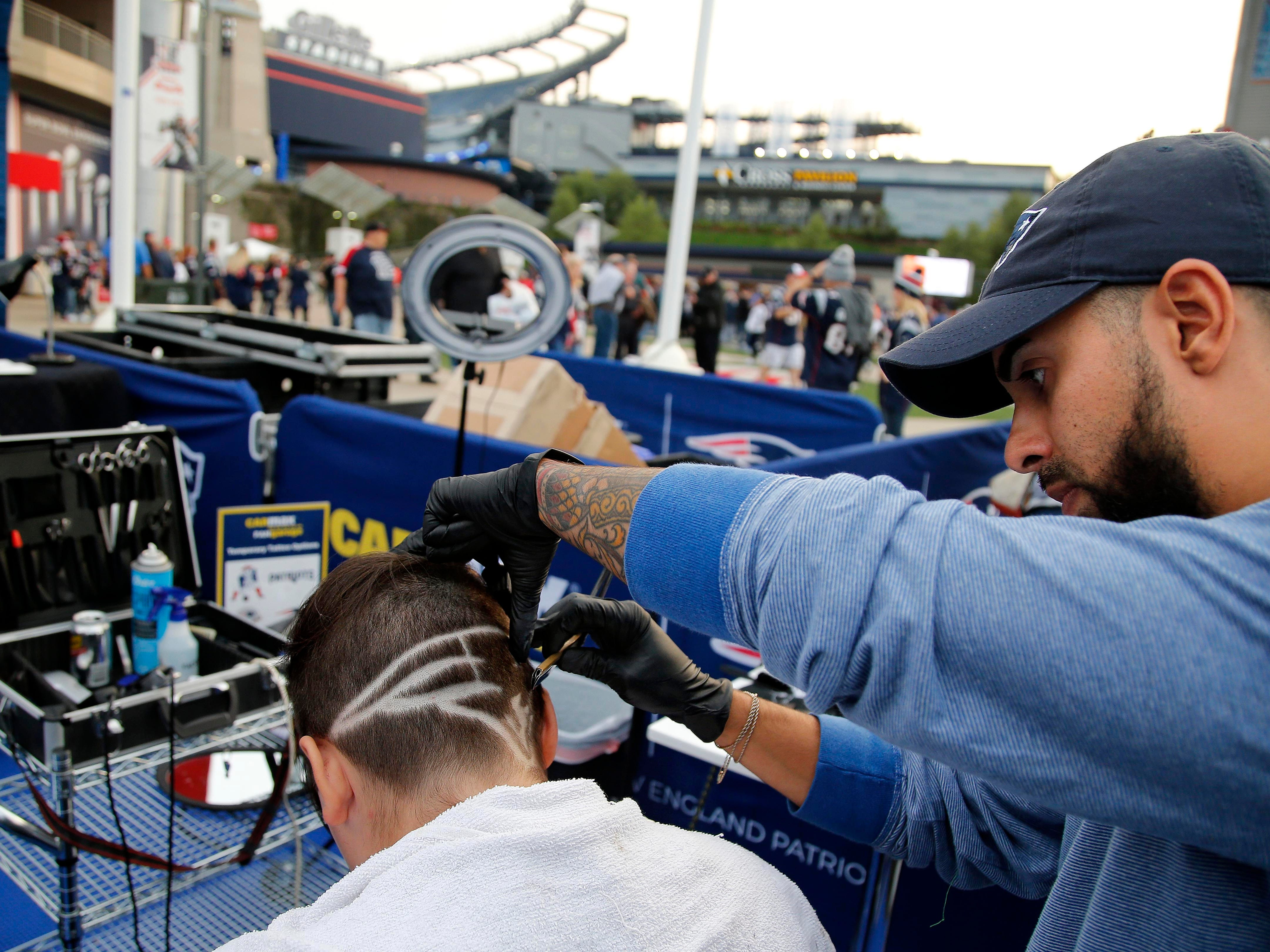 Cody Bedard has the New England Patriots logo cut into his hair by Kevin Rosas in the parking lot at Gillette Stadium before the game between the New England Patriots and the Indianapolis Colts at Gillette Stadium.