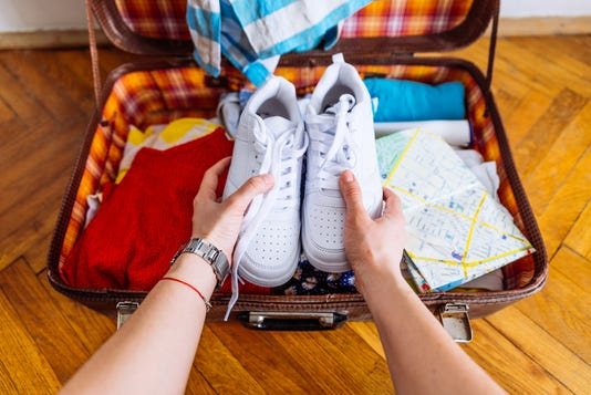 Hands Put Sneakers To Valise Packing For Trip Travel Concept