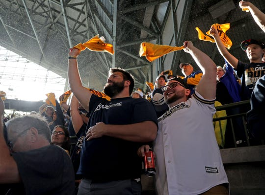 Milwaukee Brewers fans Mathew Riedel (left) and Hunter Halverson wave rally towels during game one of the 2018 NLDS playoff baseball series against the Colorado Rockies at Miller Park in Milwaukee on Oct. 4.