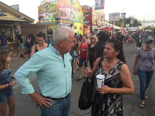 John Cox introduces himself to a voter at the Kern County Fair in Bakersfield, Calif.