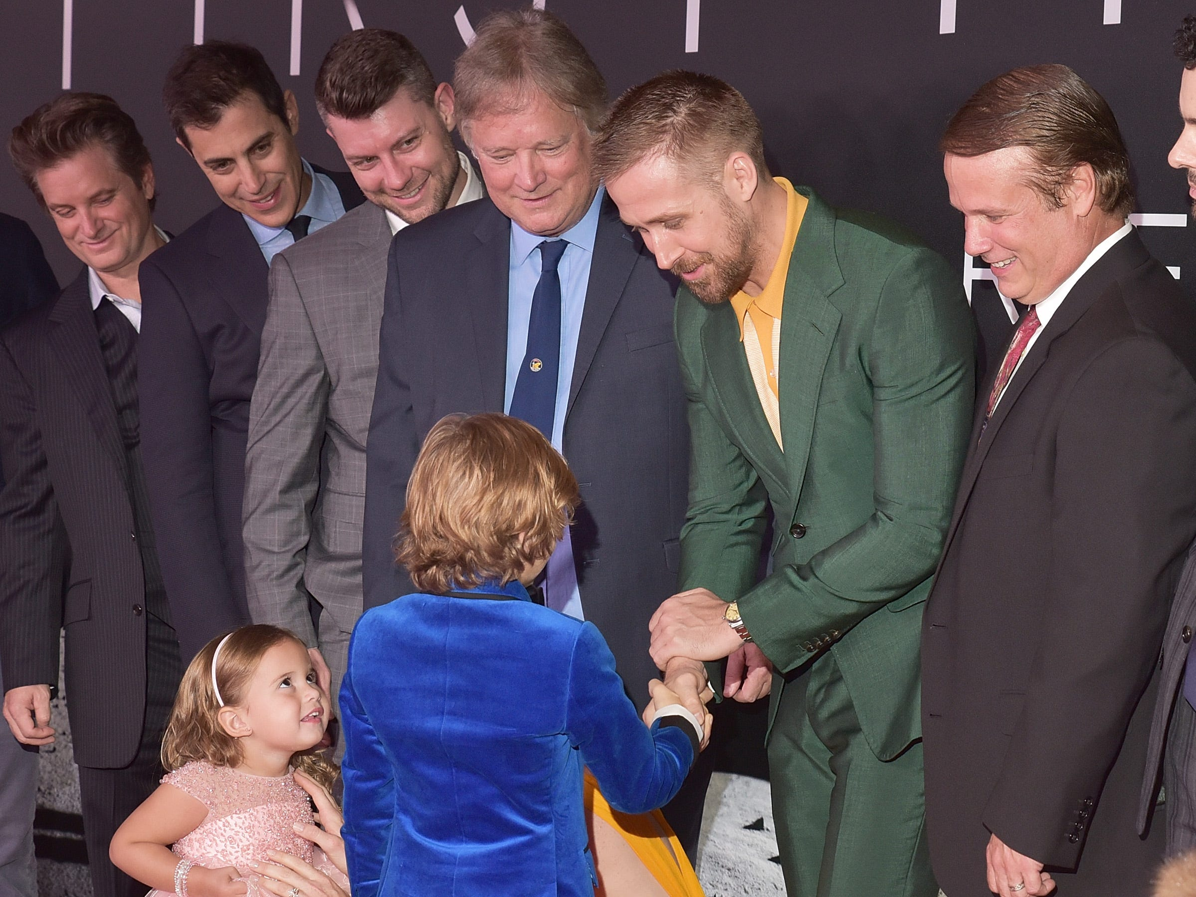 """WASHINGTON, DC - OCTOBER 04:  Actor Ryan Gosling shakes hands with child actor Gavin Warren while actor Lucy Brooke Stafford looks on at the """"First Man"""" premiere at the National Air and Space Museum on October 4, 2018 in Washington, DC.  (Photo by Shannon Finney/Getty Images) ORG XMIT: 775234726 ORIG FILE ID: 1045748526"""