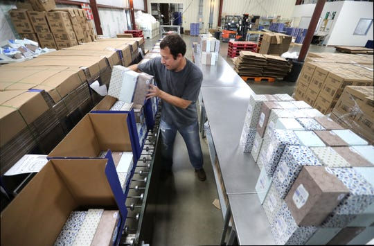 Chad Vellieux, a contract packaging employee at Apricity, packs tissue boxes into display boxes on Oct. 3 in Neenah.