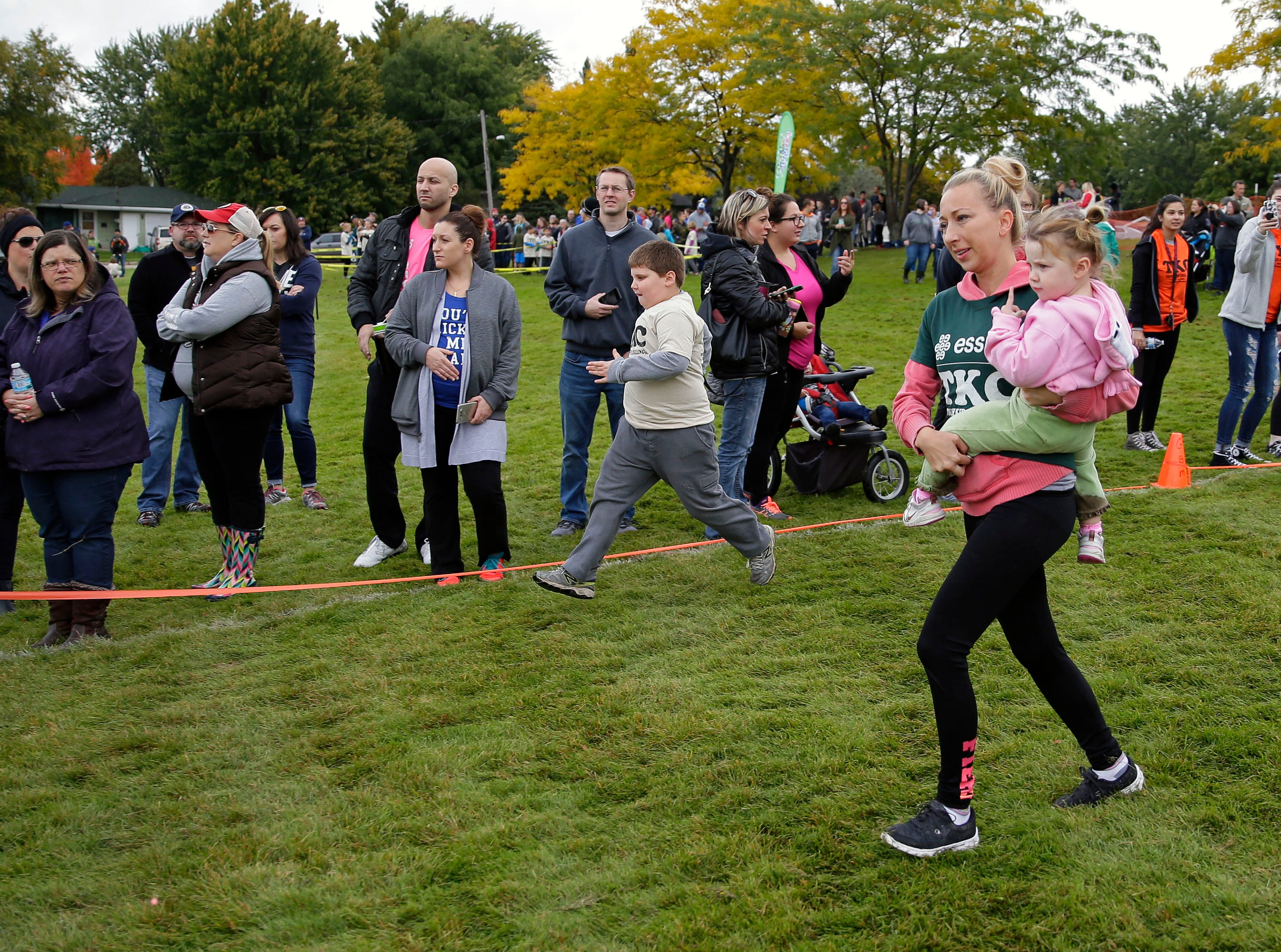 Jen Thomack carries Teagan Deering during the start as they keep an on another part of their team in front of them during the Essity Fox Valley Tough Kid Challenge Saturday, October 6, 2018, at Highlands Elementary School in Appleton, Wis. The event raised funds for Physical Education Departments in Appleton.