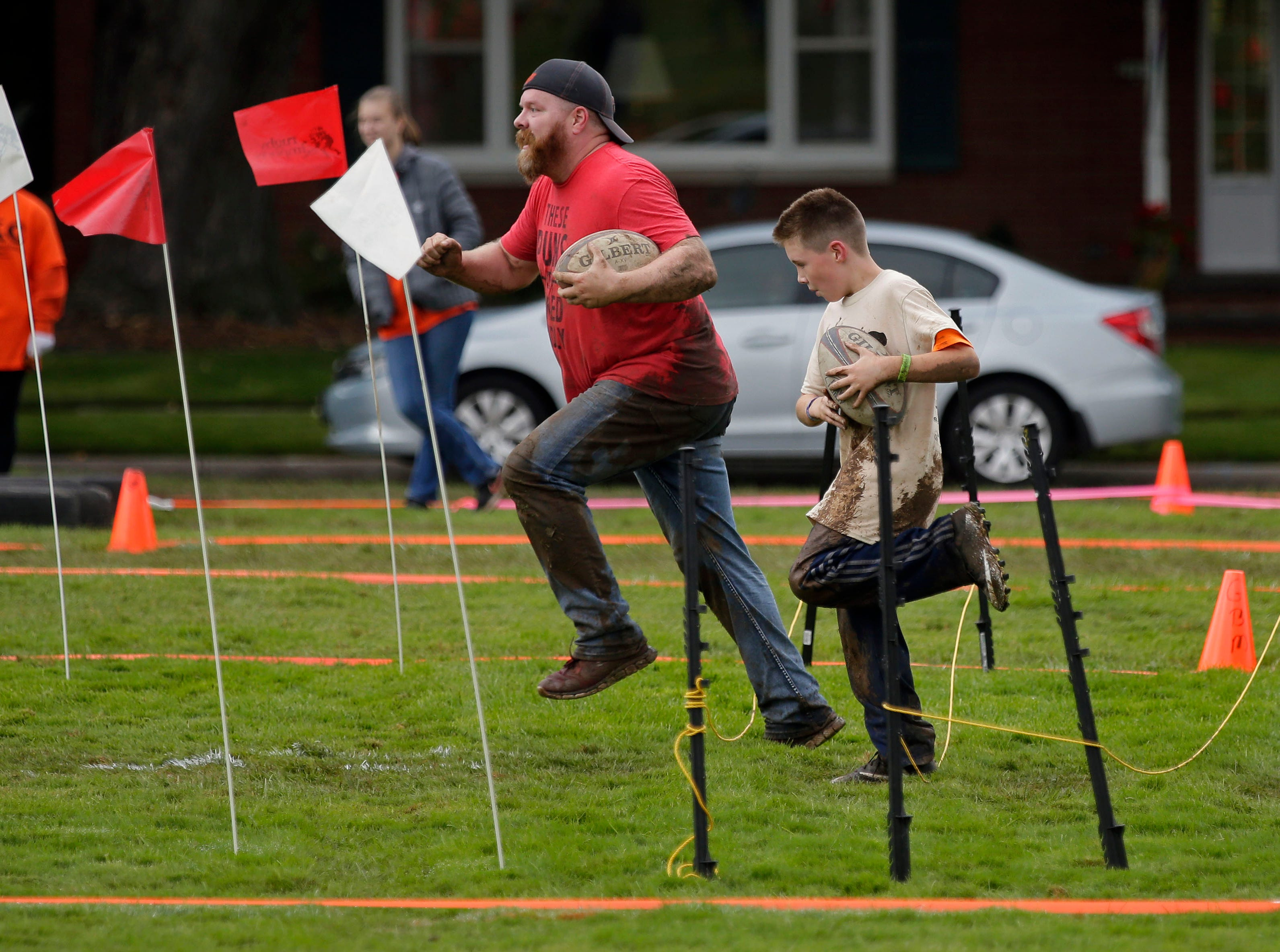 Dale Smith and his son, Rigley, tackle an obstacle as the Essity Fox Valley Tough Kid Challenge takes place Saturday, October 6, 2018, on a course at Highlands Elementary School in Appleton, Wis. The event raised funds for Physical Education Departments in Appleton.