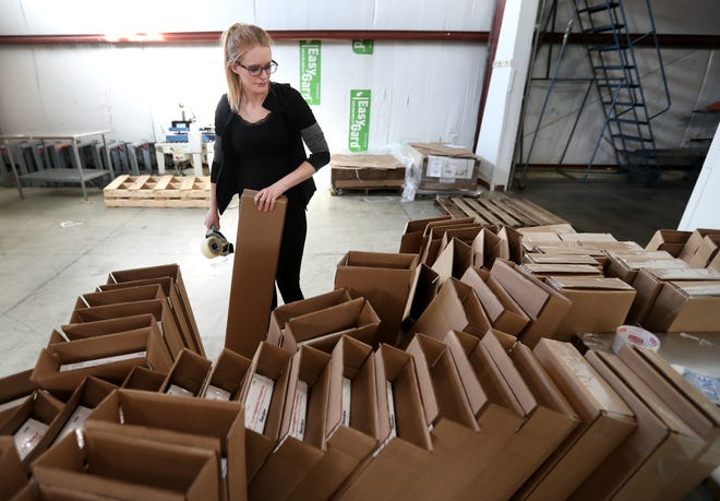 Alexis Polar, a contract packaging employee at Apricity, tapes boxes shut on Oct. 3 in Neenah.