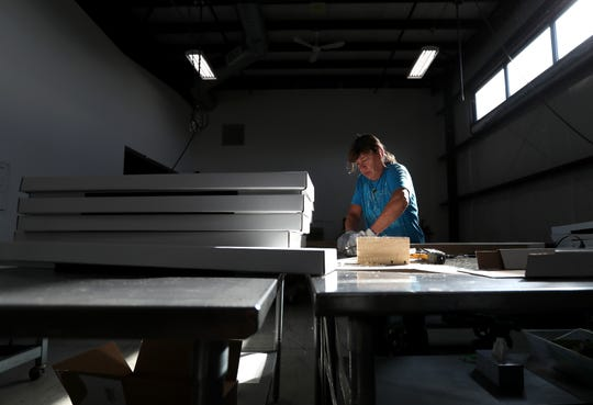 Chris Rasmussen, a contract packaging employee at Apricity, folds boxes Oct.3 in Neenah.
