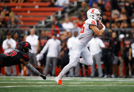 Illinois running back Mike Epstein gets away from Rutgers defensive back Kiy Hester on the way to a touchdown during the second half of an NCAA college football game Saturday, Oct. 6, 2018, in Piscataway, N.J. Illinois won 38-17 (AP Photo/David Boe)