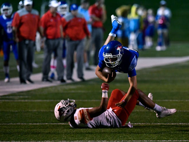 Cougars running back Xavier Wishert dives over Lubbock Coronado safety Jason Ramos during Friday's game at Shotwell Stadium Oct. 5, 2018. Final score was 42-23, Mustangs.