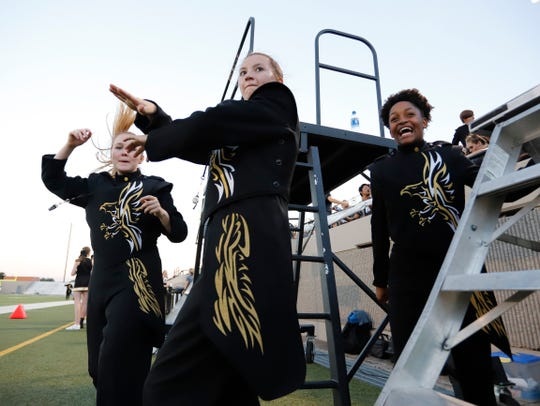 Eagle band drum majors Kaylee Brentle, Jada Williams and Tavia Wilson dance to the football team's warmup music. The Abilene High School Eagles played the L.D. Bell Blue Raiders at Pennington Field in Bedford.
