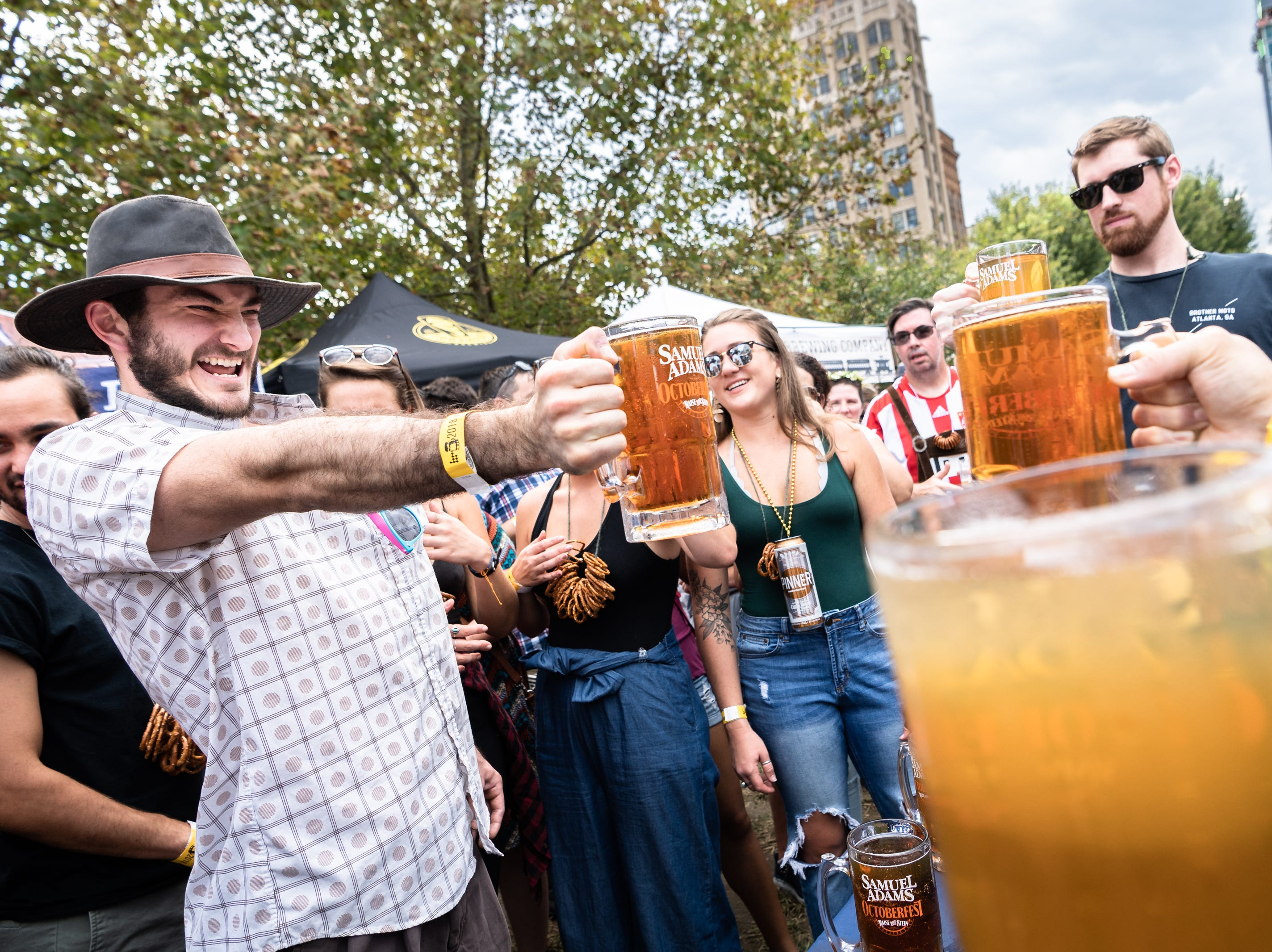 Brian Starnes grimaces at he struggles to hold up his mug during their stein hoisting competition at the 10th annual Asheville Oktoberfest at Pack Square Park Saturday, Oct. 6, 2018.