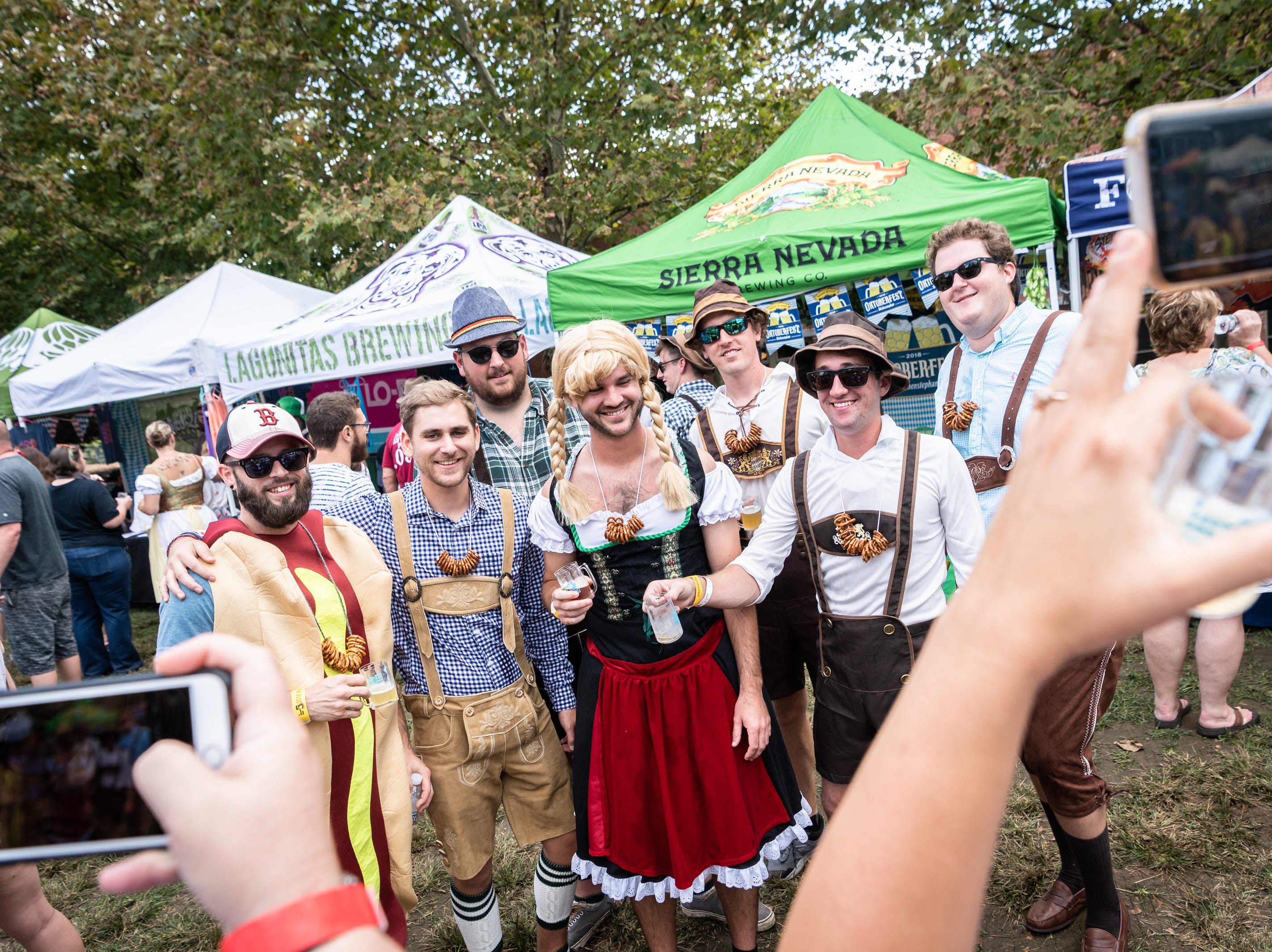 A group of festively-dressed attendees of the 10th annual Asheville Oktoberfest pose for a photo took place at Pack Square Park Saturday, Oct. 6, 2018.